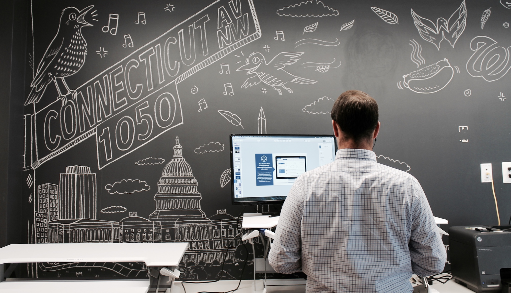 A Quorum employee using a standing desk in front of a chalk-art decorated wall.